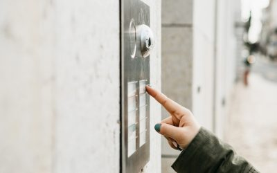 Close up of a female hand pressing a intercom button on a building.