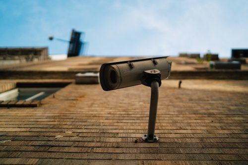 a cctv security camera attached to a brick wall
