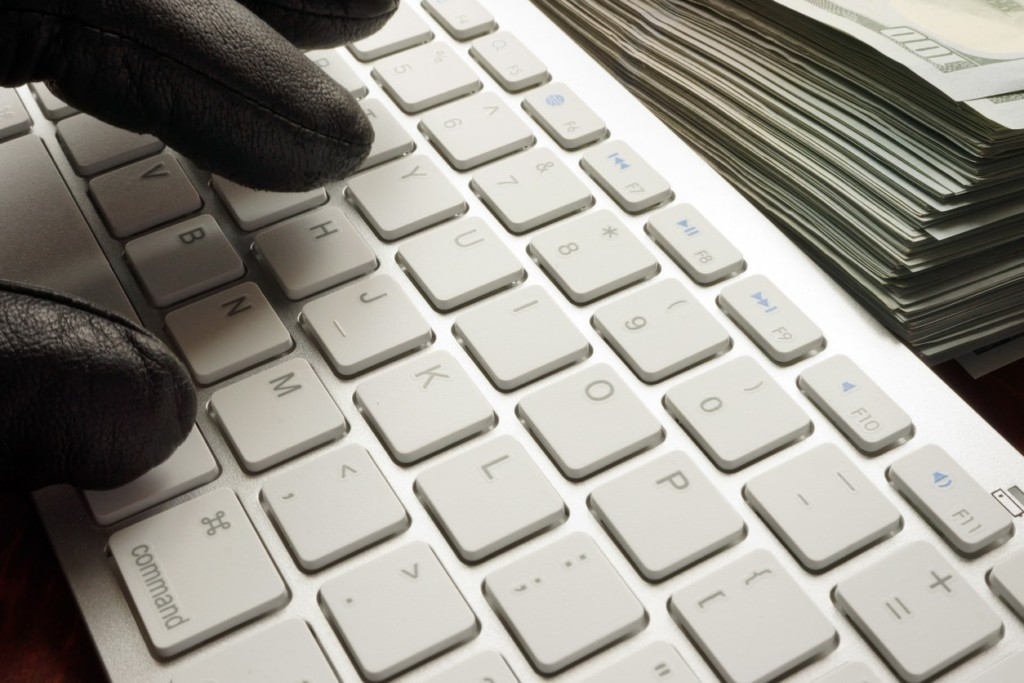 Hand in black glove types on computer keyboard with cash next to it